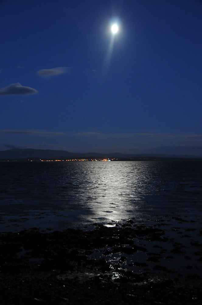 Picture of the full Moon high over a sea loch, the lights of a village in the distance