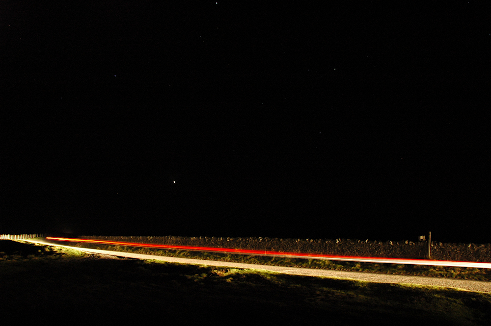 Picture of a country lane at night, the lights of a passing car illuminating the night