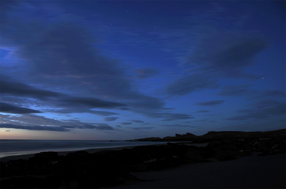 Picture of a bay with a beach at very last light, the first stars starting to appear in the sky