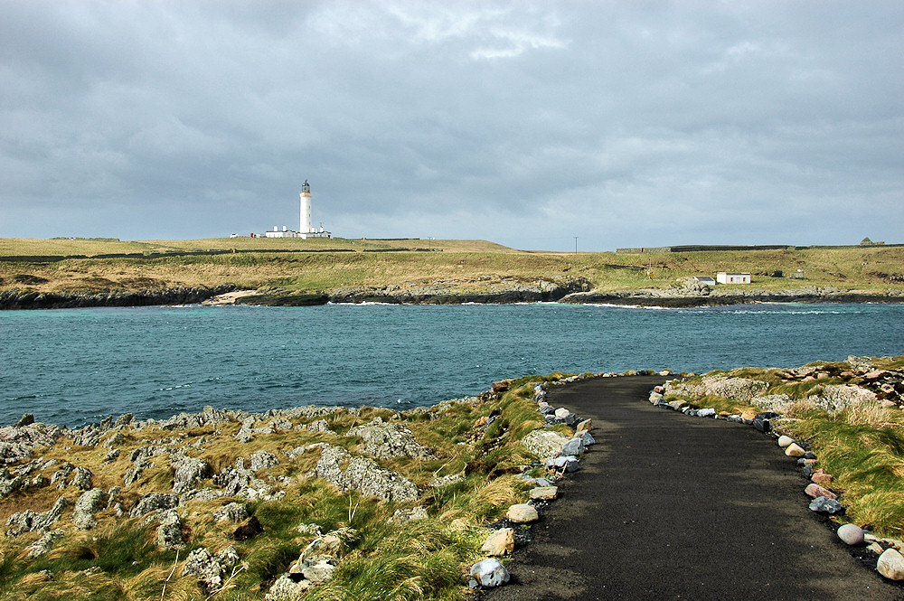 Picture of a view to a small island with a lighthouse from a coastal path