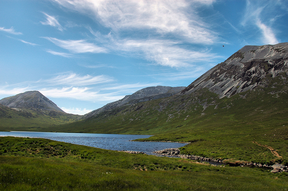 Picture of three mountains towering over a loch