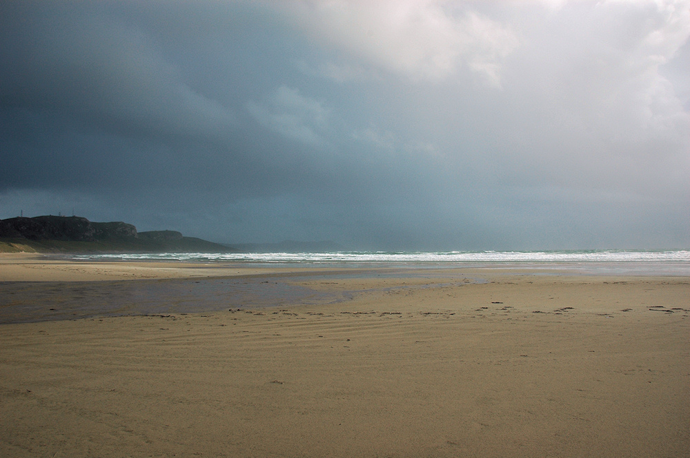 Picture of a bay with a sandy beach, heavy rain approaching