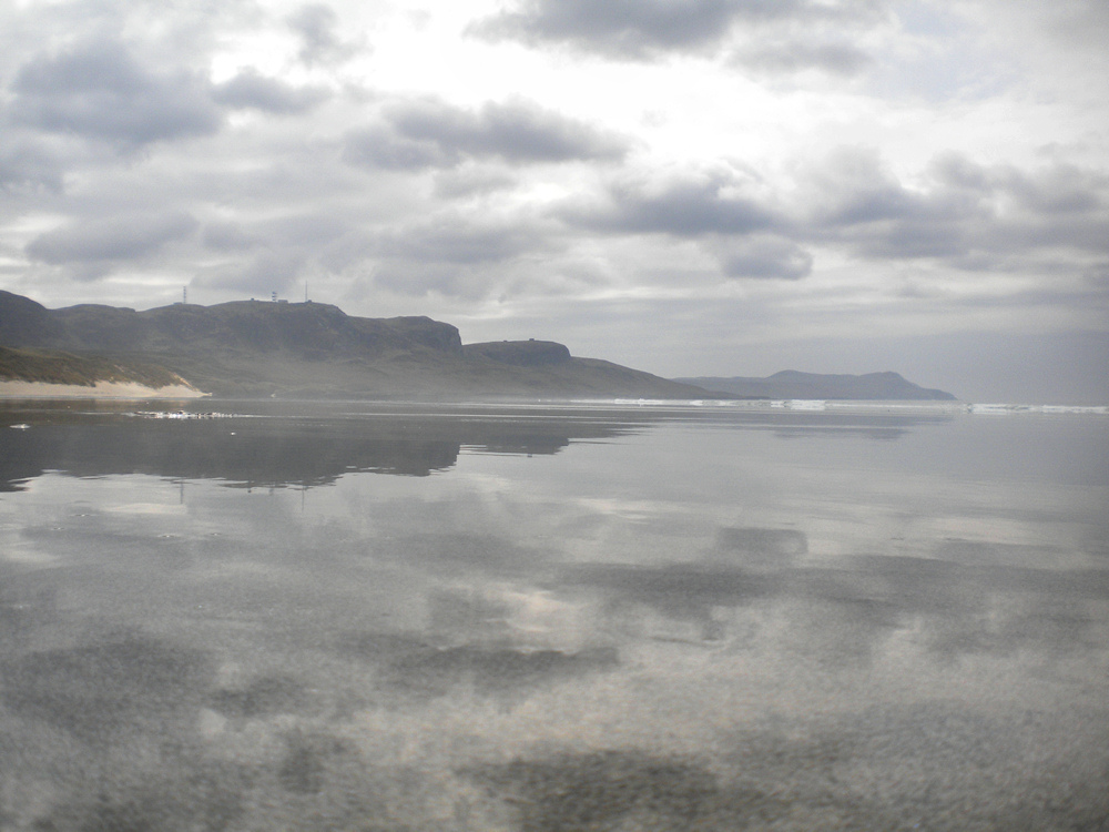 Picture of a wet beach reflecting the sky and landscape around