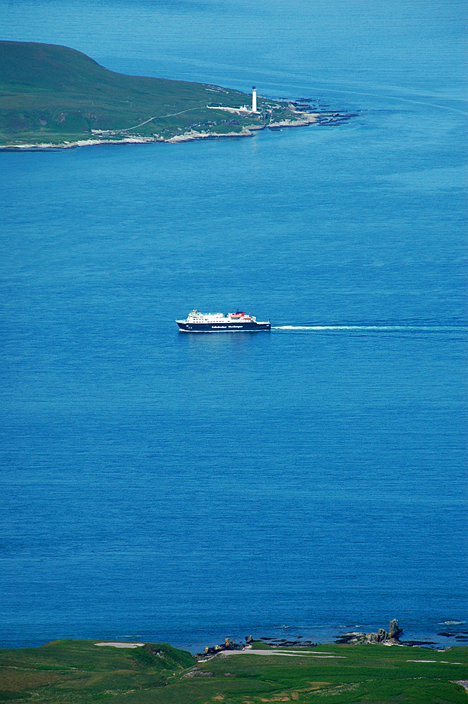 Picture of a lighthouse and a passing ferry at the entrance to a sound, seen from a mountain top