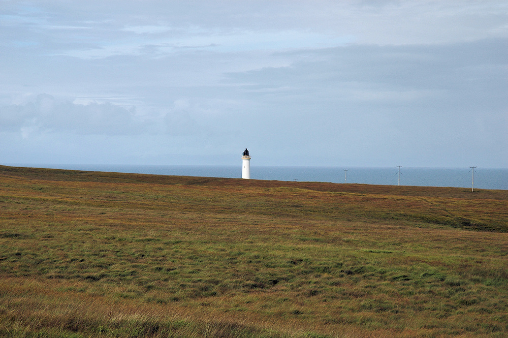 Picture of a lighthouse in the distance behind some low hills