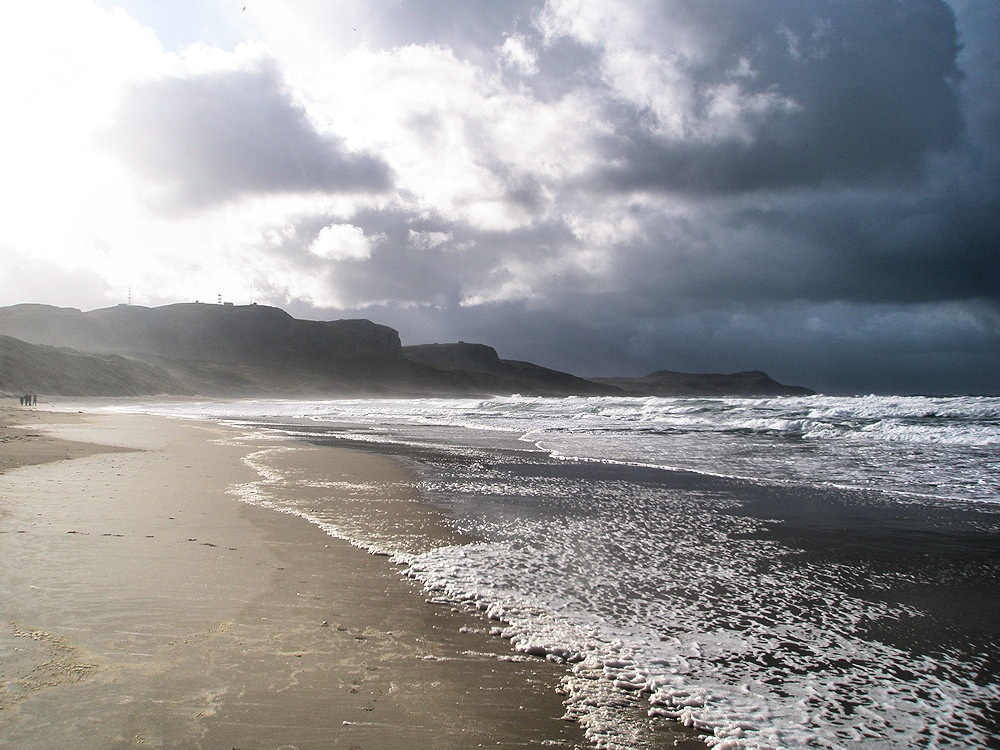 Picture of a beach with waves rolling in, dark clouds one side, bright sunshine the other side