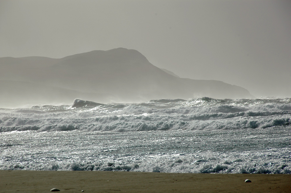 Picture of waves rolling into a bay, heavy spray and haze in the air