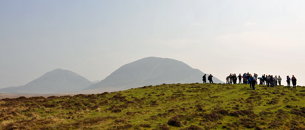 Picture of a group of walkers on a low hill, two high hills behind them