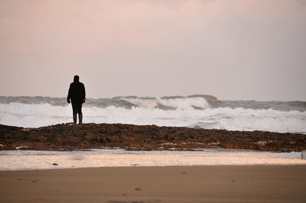 Picture of a man standing on rocks on a beach watching the waves rolling in