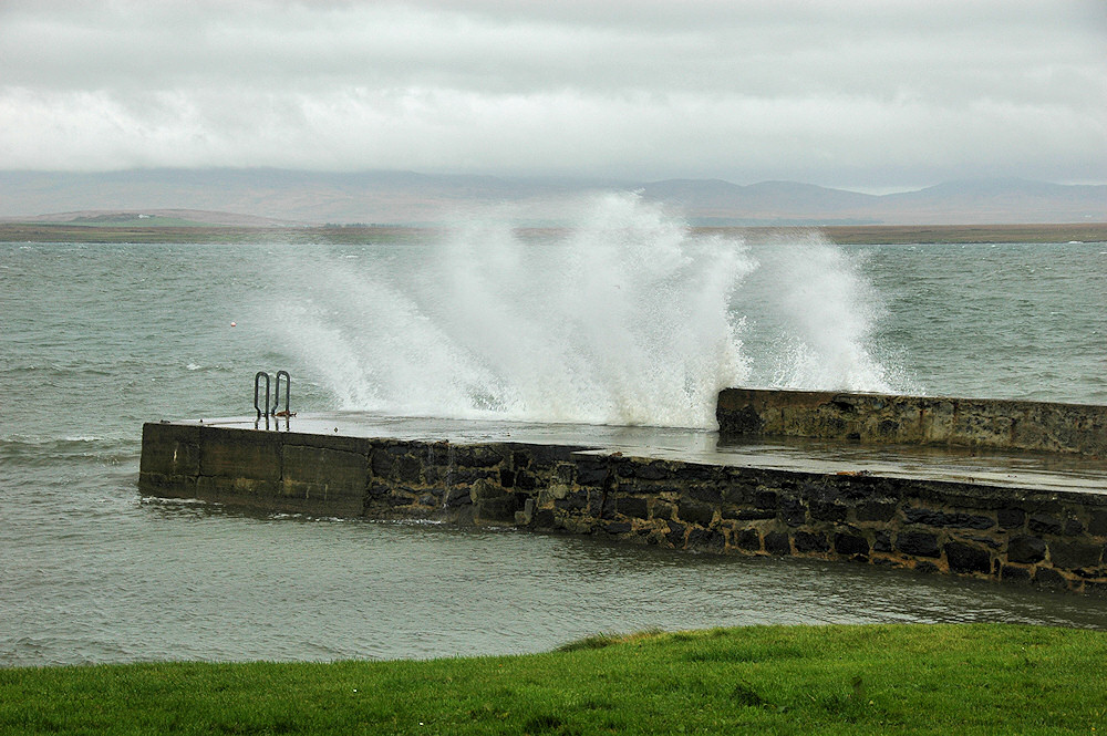 Picture of a wave breaking over a small stone pier
