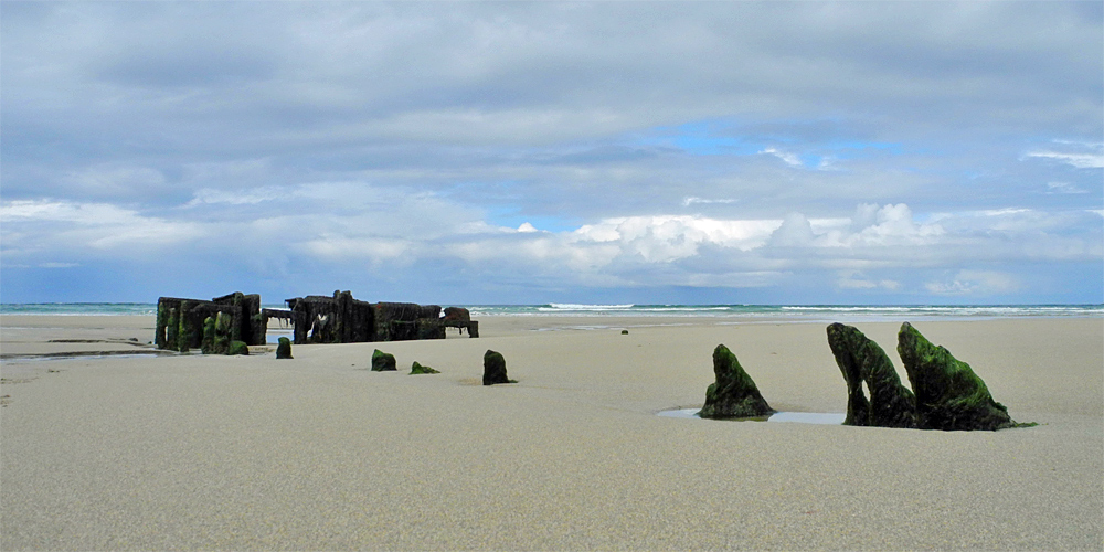 Picture of a wreck embedded in a beach at low tide