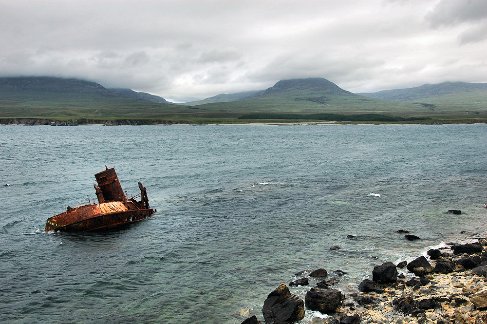 Picture of the rusting wreck of a ship just of the shore of a sound on a cloudy day