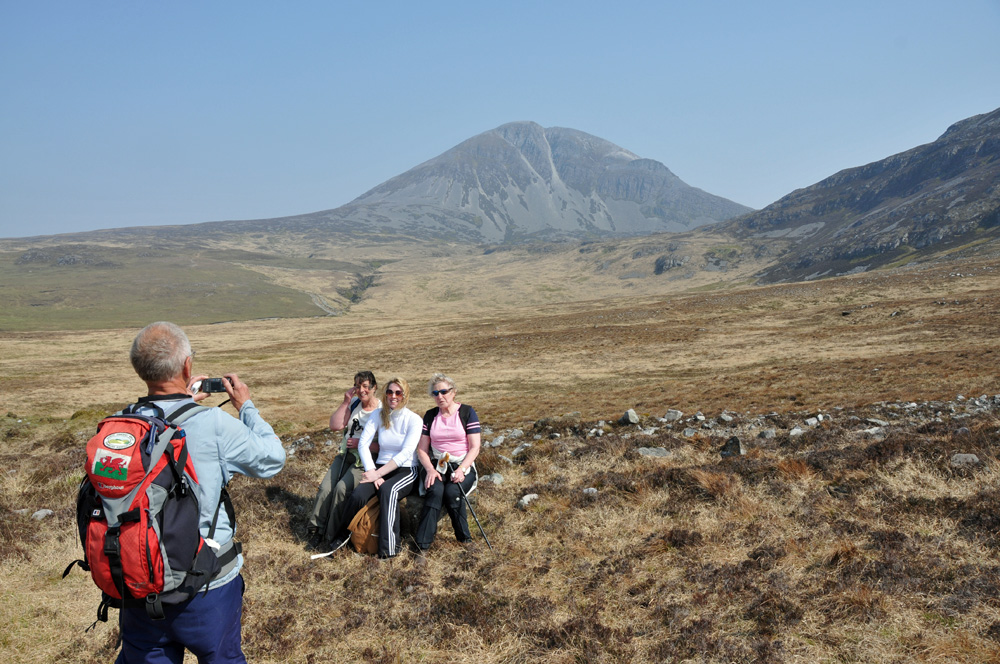 Picture of a man with Welsh dragon on his backpack taking a picture of three women in front of a mountain