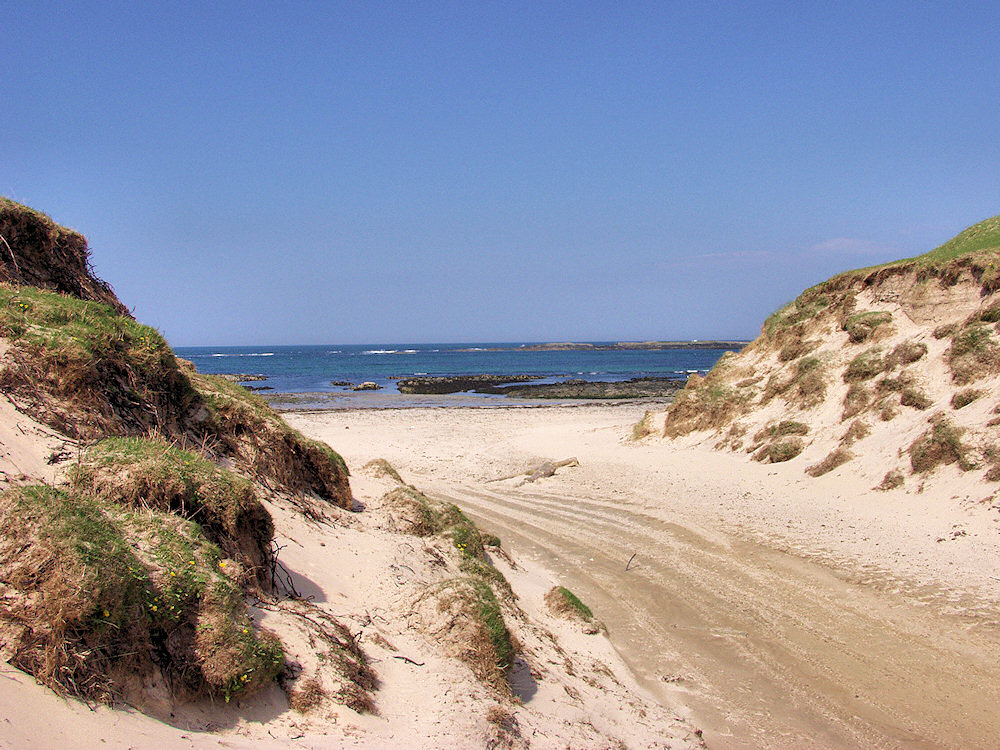 Picture of a gap in sand dunes leading to a beach