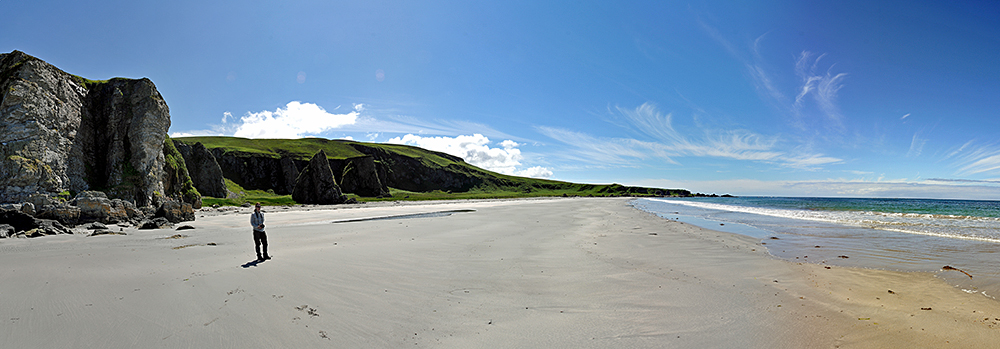 Picture of a panoramic view over a sandy beach, a woman standing on the beach
