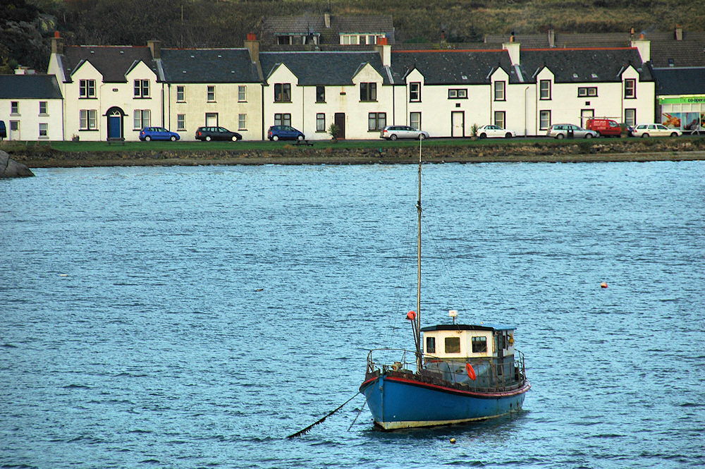 Picture of a blue boat moored in a small bay, houses of a village on the shore
