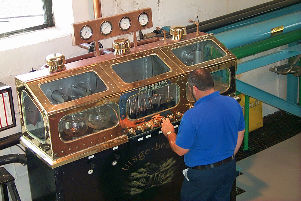 Picture of a whisky distillery worker adjusting setting at the spirit safe