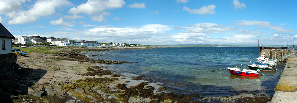 Picture of a panoramic view over a pier and a distillery at a sea loch