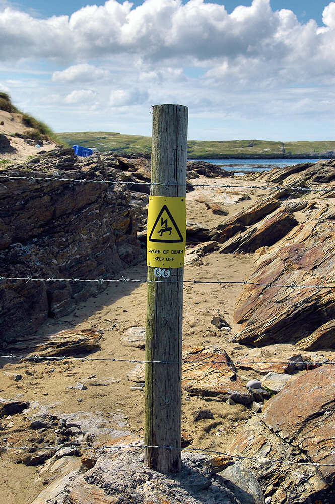 Picture of an on electricity pole with warning sign converted to a fence post