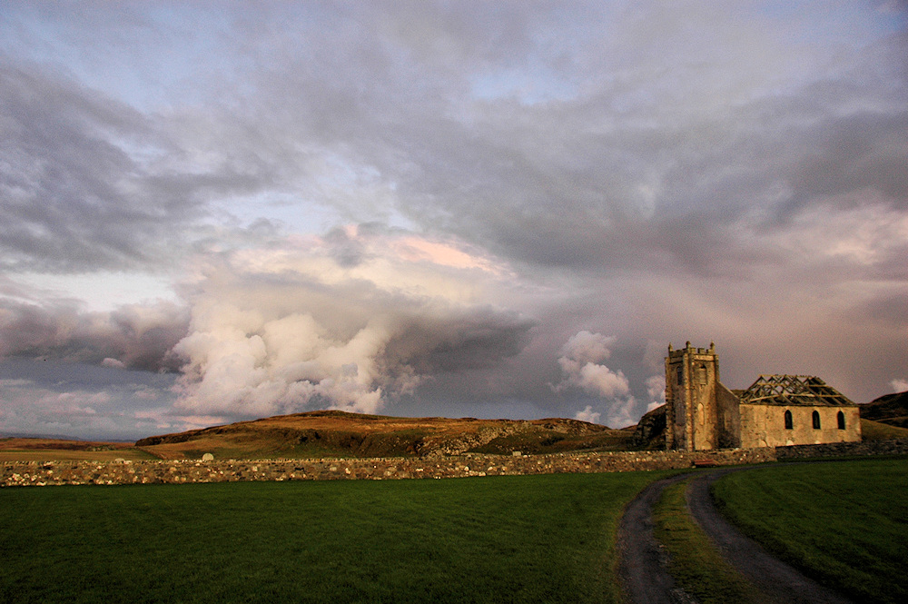 Picture of a church ruin in the evening light, dramatic clouds in the sky