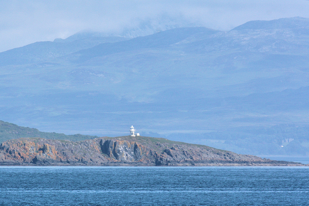 Picture of a small lighthouse on an island, hills of another island in the background
