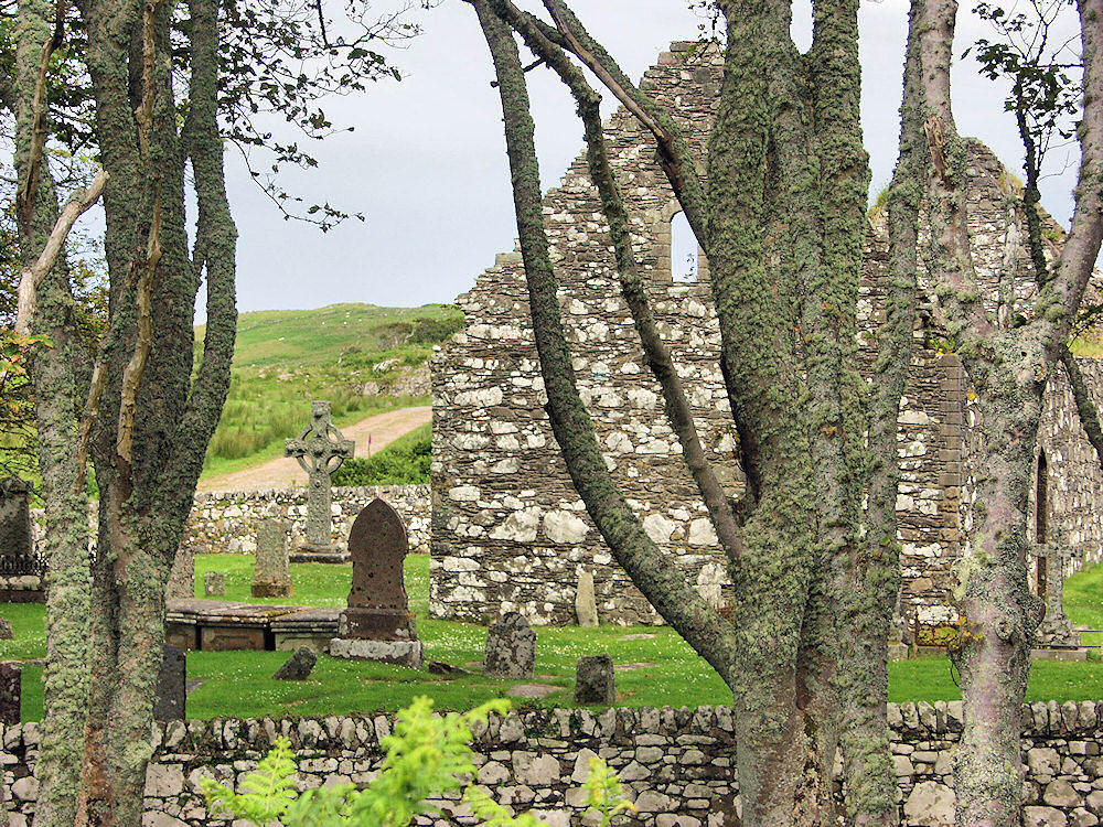 Picture of a Celtic cross and a church ruin, seen through trees