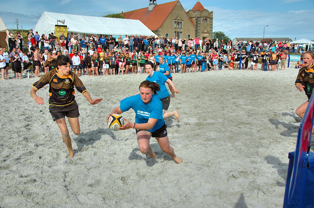 Picture of a female beach rugby player on her way to a try