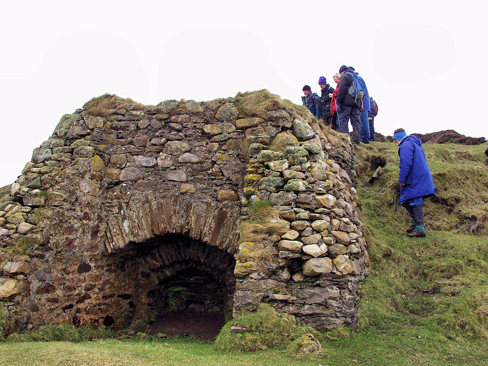 Picture of the remains on an old lime kiln, a group of walkers looking at it