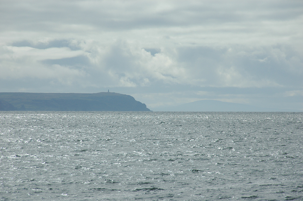 Picture of a view across the sea with a mull and another island in the distance