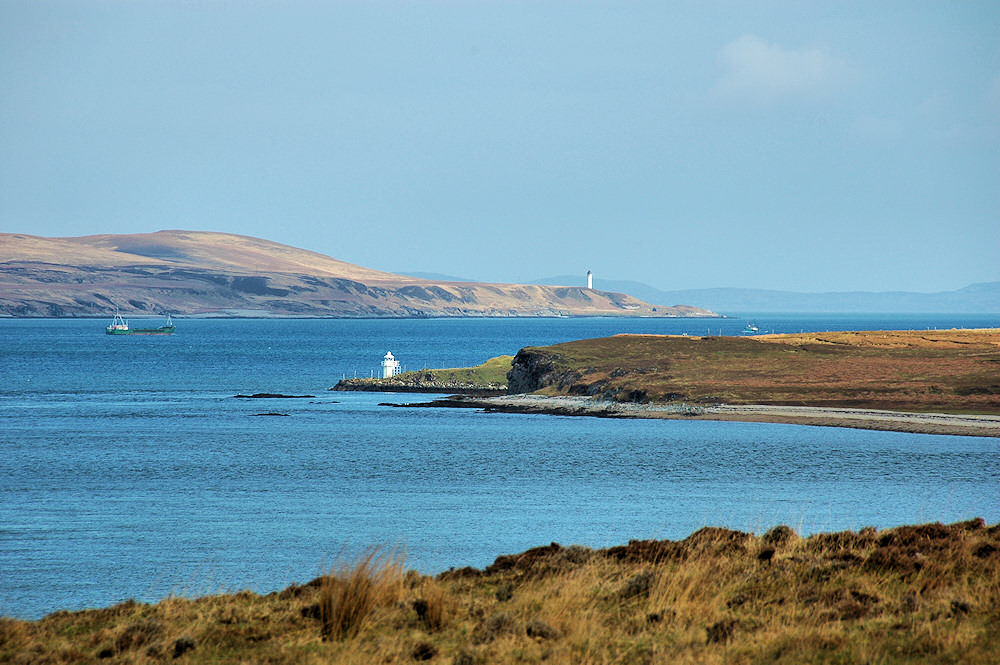 Picture of a view over a sound between two islands, two lighthouses and two ships in view
