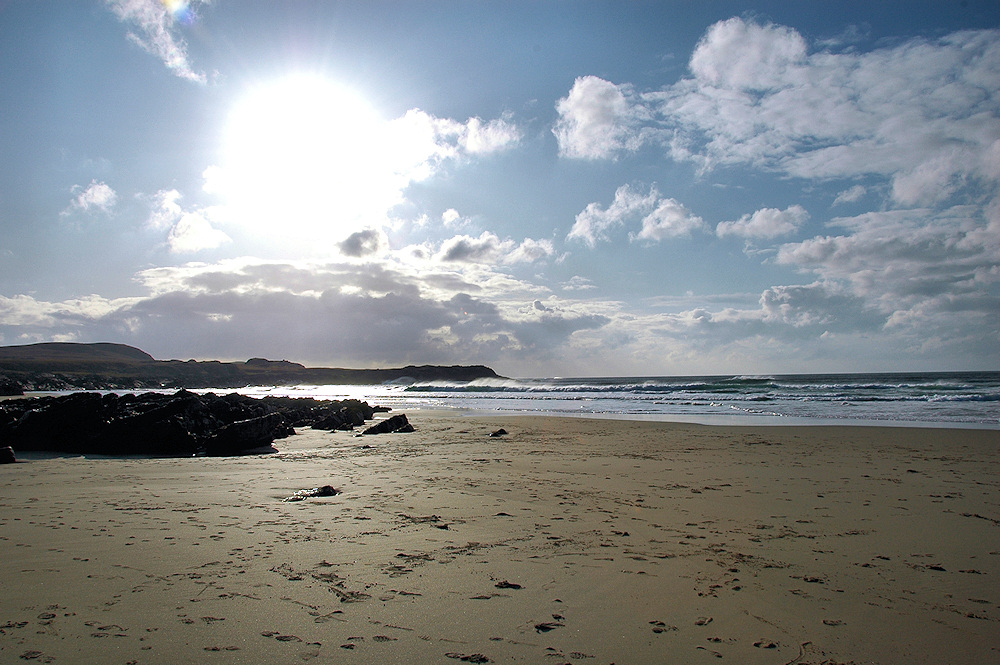 Picture of a bright sun as well as some clouds over a bay with a sandy beach around rocks