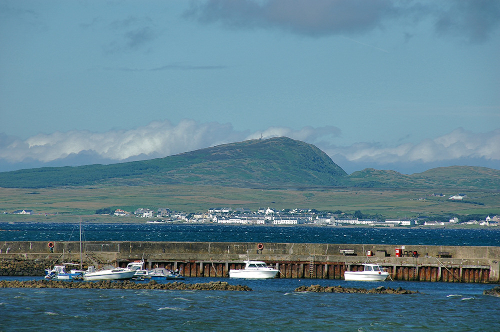 Picture of a view across a sea loch towards a village, a small harbour with a pier in the foreground