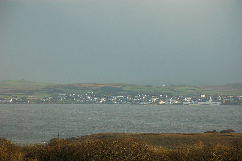 Picture of a coastal village with rain clouds moving away and the sun breaking through