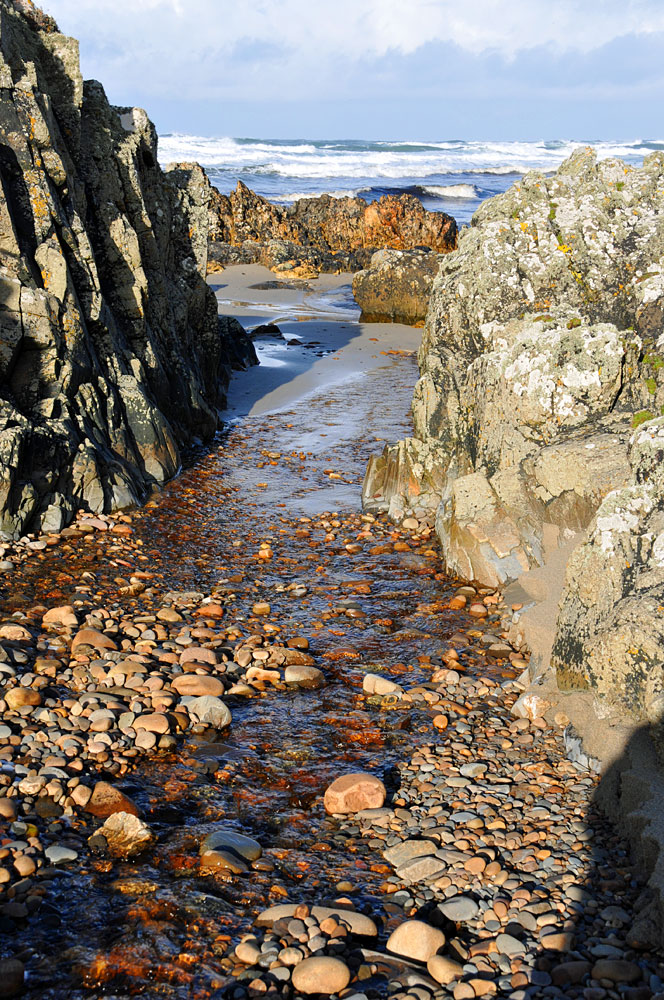 Picture of a small stream flowing through rocks and stones towards a beach