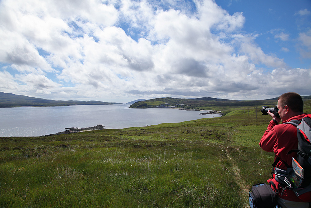 Picture of a man in walking gear taking pictures of a distillery at a sound between two islands