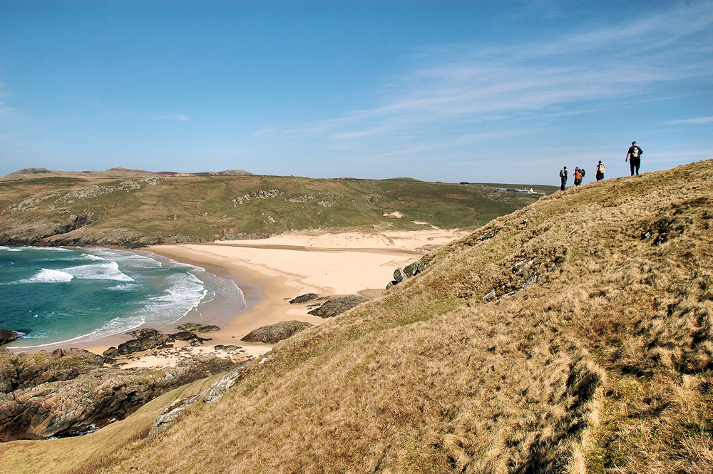 Picture of a group of walkers approaching a bay with a sandy beach