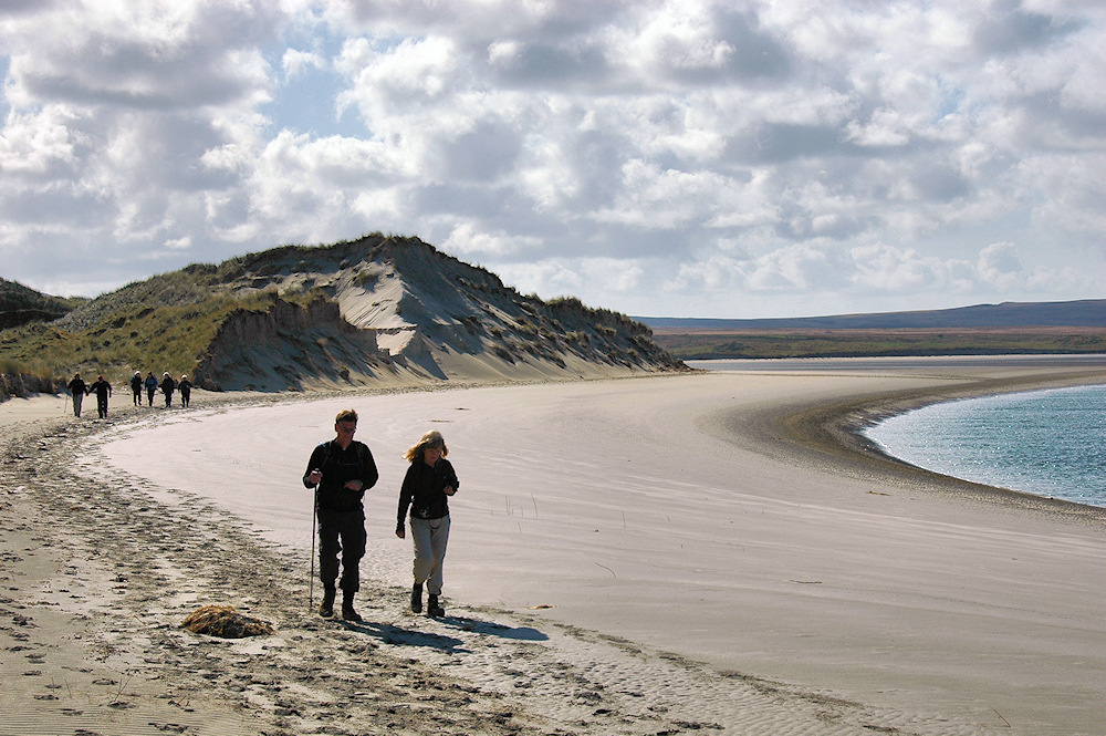 Picture of walkers on a beach with dunes behind, the entrance to a sea loch in the background