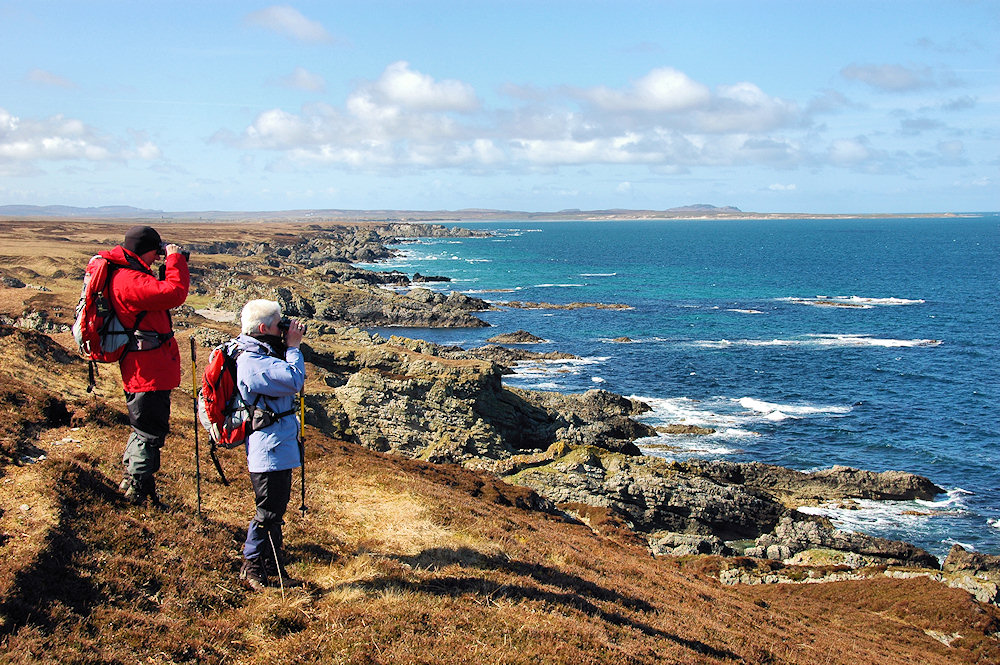 Picture of two walkers with binoculars looking out to sea on a rugged coastline