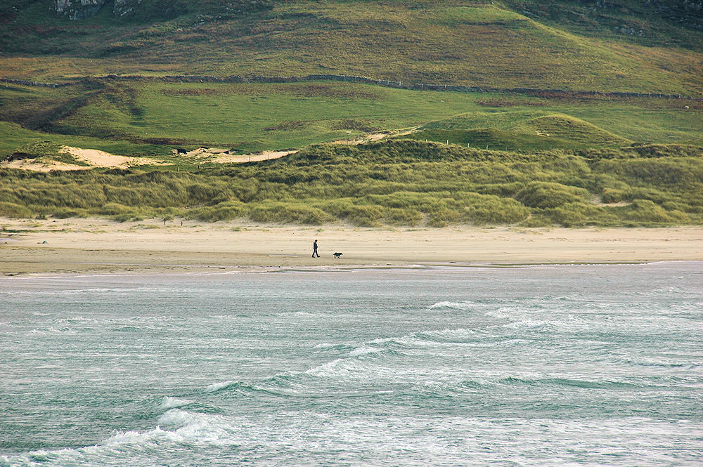 Picture of a man walking a dog on a beach, dunes and hills in the background