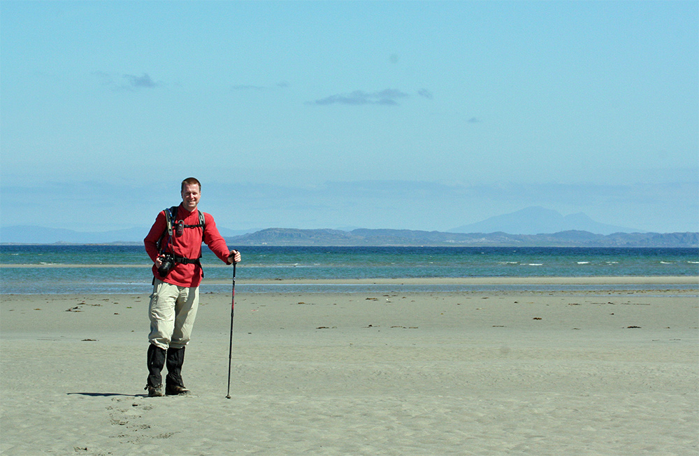 Picture of a man standing on a beach, neighbouring islands in the background