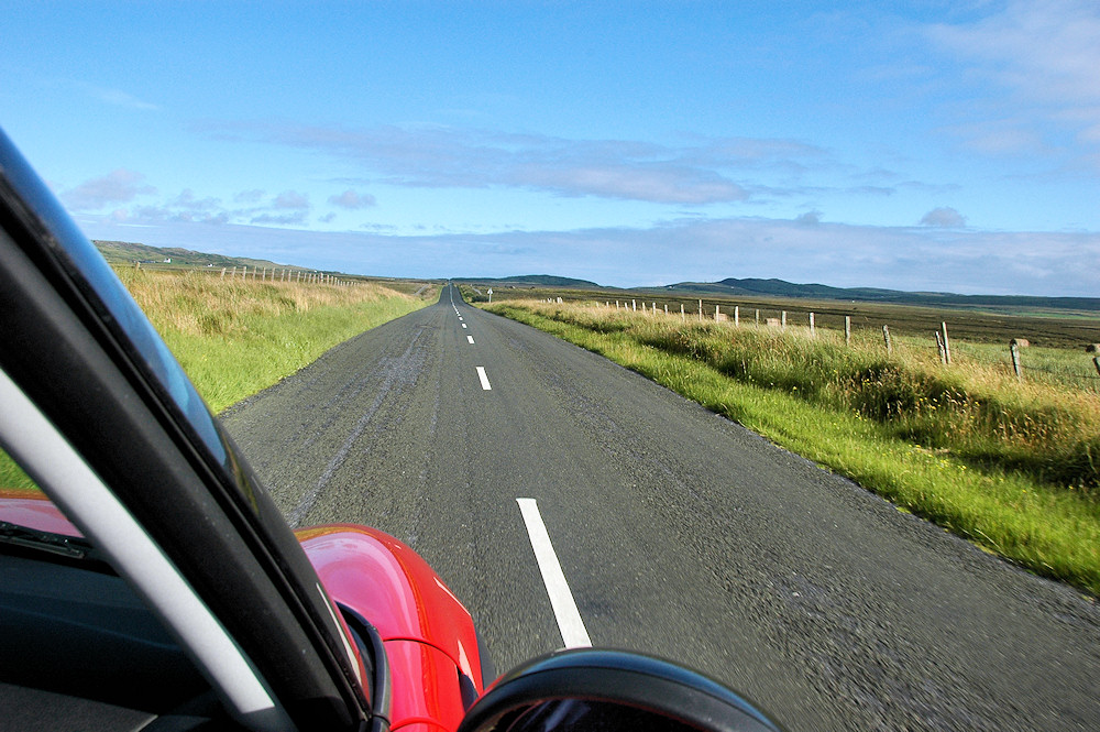 Picture of a view from a car along a very long straight road