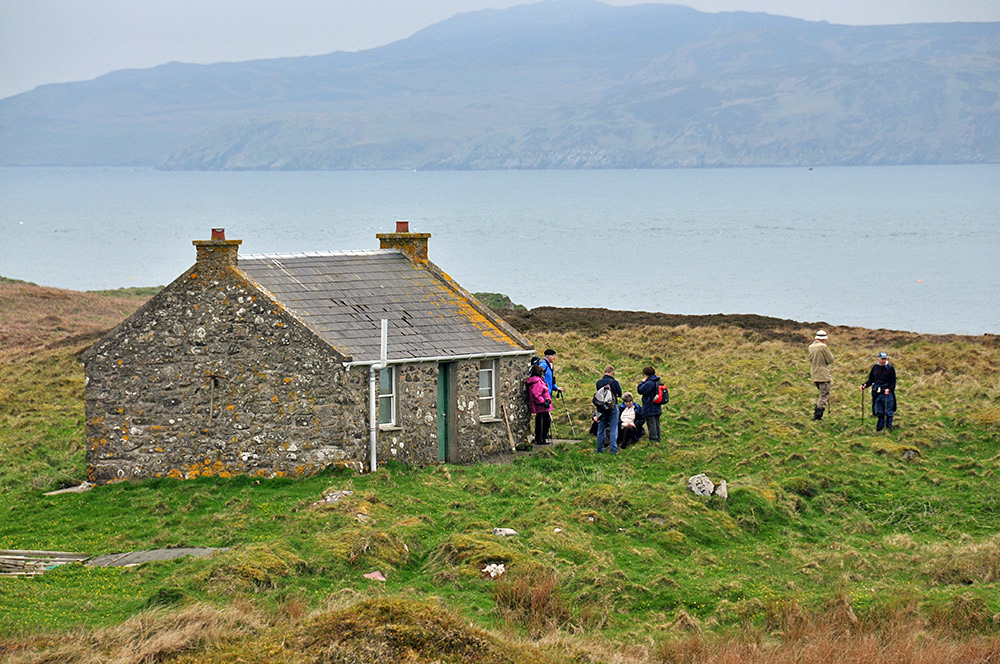 Picture of a small single story cottage on a small island, a few walkers standing around it