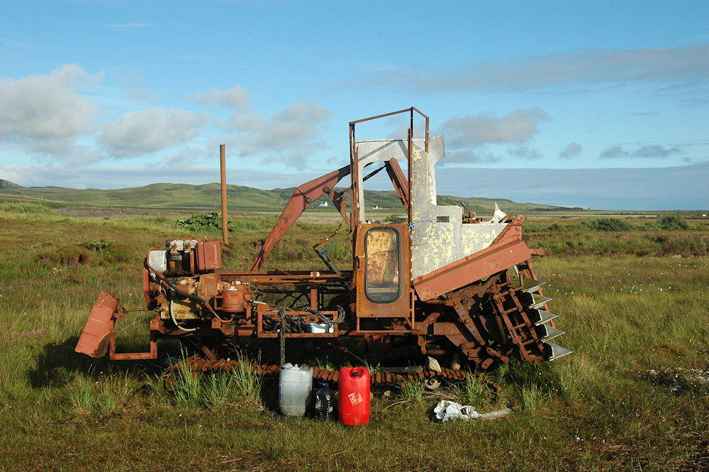 Picture of a rusty peat cutting machine near peat bogs