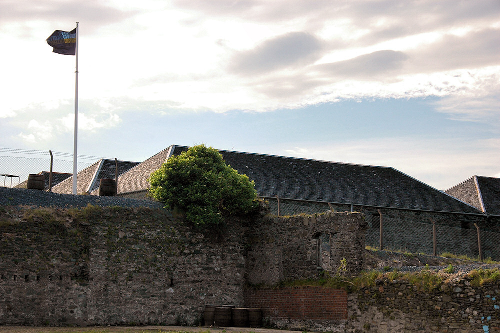 Picture of some old distillery warehouses behind ruined walls of a building