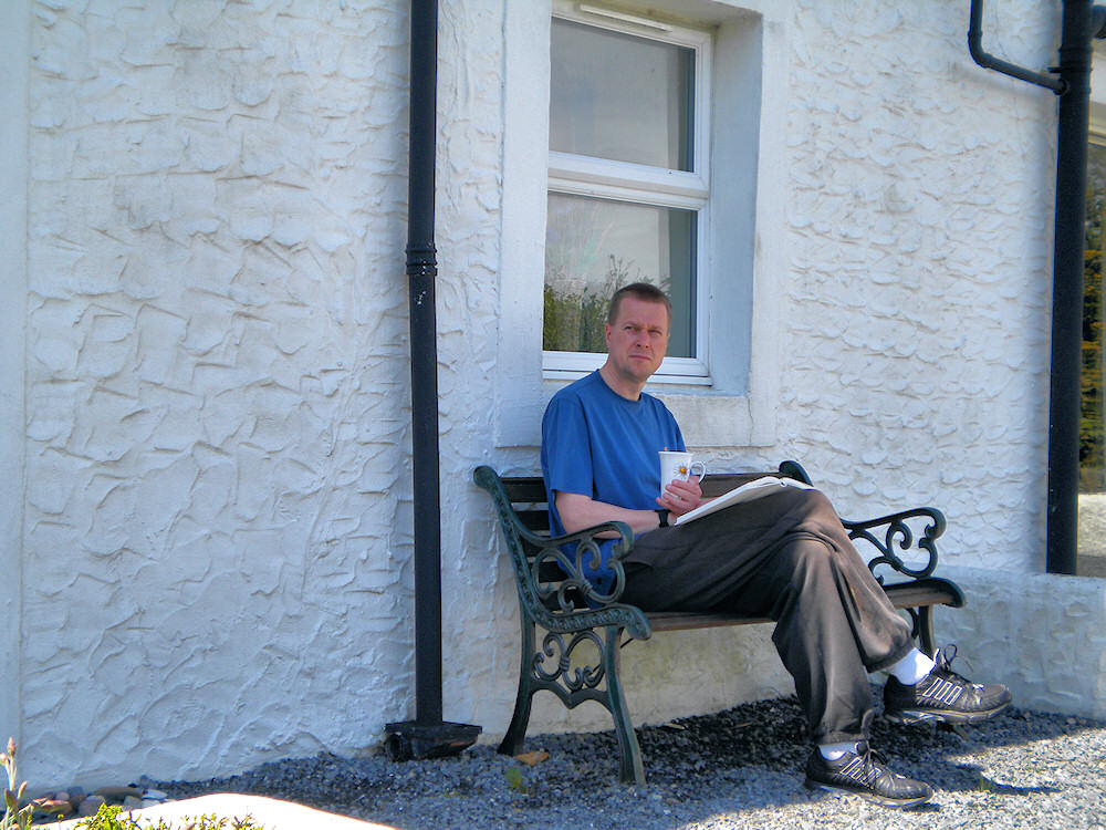 Picture of a man sitting on a bench outside a cottage, reading a book