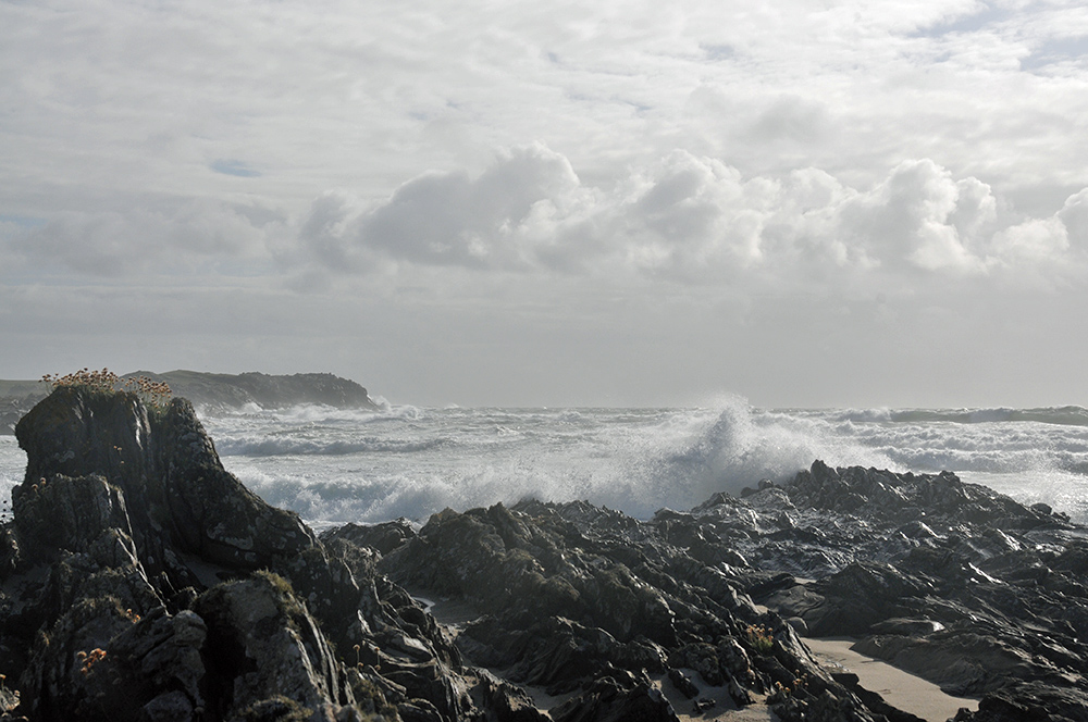 Picture of a bay with waves rolling in, breaking over rocks