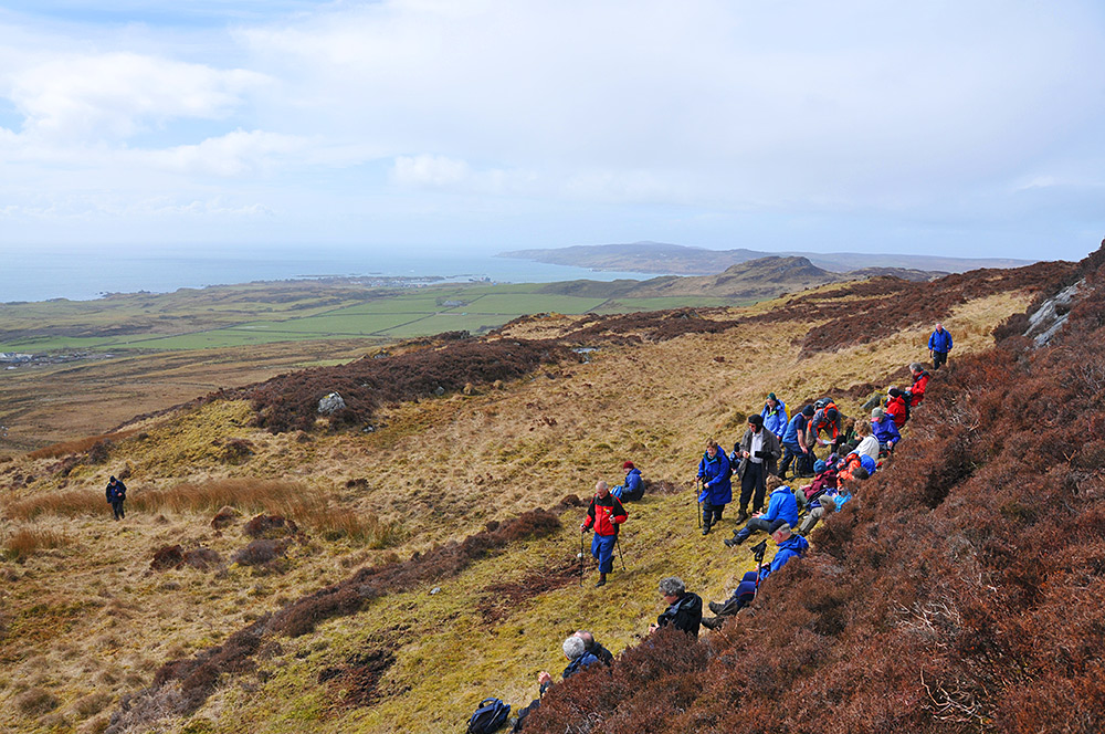 Picture of a group of walkers settling down for a break on a hillside high above a shoreline