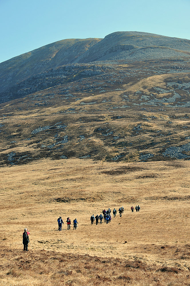 Picture of a group of walkers approaching a mountain they plan to climb