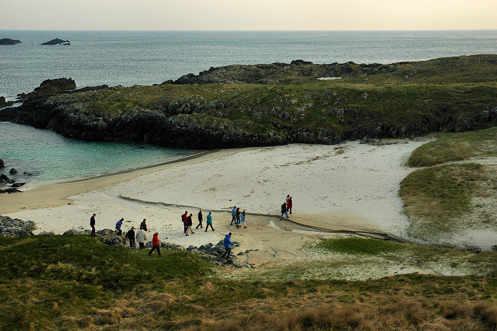 Picture of a group of walkers crossing a small beach