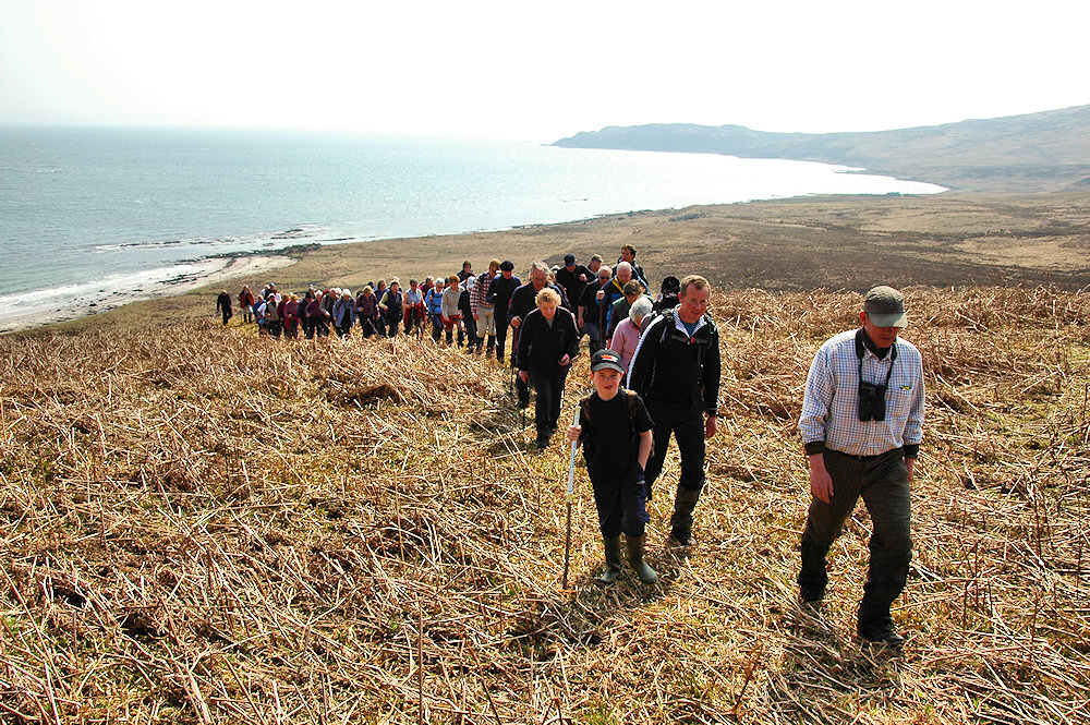 Picture of a large group of walkers ascending a hillside, a bay in the background